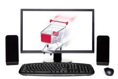 Carrinho de compras que sai do computador de secretária Foto de Stock