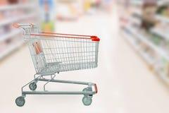 Carrinho de compras vermelho vazio com o supermercado abstrato do borrão foto de stock