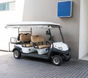 Carrinho de golfe branco com bancos traseiros na construção pública Imagens de Stock Royalty Free