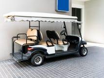 Carrinho de golfe branco com bancos traseiros na construção pública Imagem de Stock