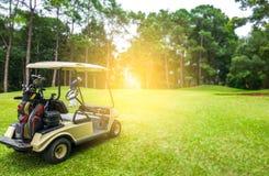 Carrinho de golfe e jogador de golfe no fairway no campo de golfe fotografia de stock royalty free