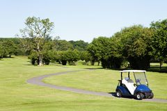 Carrinho de golfe em um caminho de um campo de golfe Foto de Stock