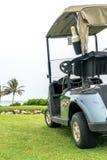 Carrinho de golfe verde estacionado no campo de golfe fotografia de stock
