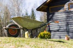 Carrinho de mão do jardim na parte dianteira da casa da exploração agrícola Foto de Stock