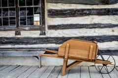 Carrinho de mão de madeira antigo, cabana rústica de madeira fotografia de stock