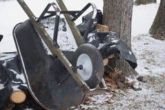 Carrinho de mão de roda na pilha do log no inverno fotos de stock
