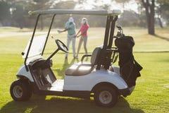 Carrinho do golfe no campo durante o dia ensolarado imagens de stock