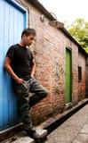 Carrinho do homem de encontro a uma porta velha e só asiáticos Imagem de Stock