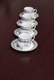 Carrinho gracioso de quatro copos de café em uma tabela Fotos de Stock