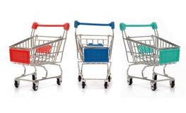 Carrinhos de compras diferentes das cores com reflexão no fundo branco Fotos de Stock Royalty Free