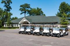 Carrinhos de golfe e clube no campo de golfe atarracado do lago Imagem de Stock Royalty Free