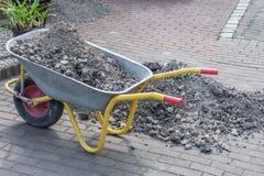 Carriola con i detriti e la terra di costruzione durante i lavori di costruzione secondari in un giardino fotografie stock