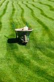 Carriola con una certa attrezzatura di giardinaggio su un'erba verde del taglio fresco immagini stock