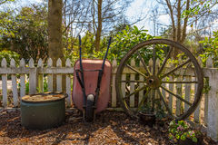 Carriola del giardino ed e vecchia ruota del carretto di manzo Fotografie Stock Libere da Diritti