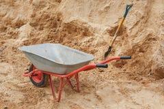 Carriola della costruzione riempita di sabbia una pala Immagini Stock Libere da Diritti