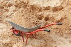 Carriola della costruzione riempita di sabbia una pala Immagine Stock