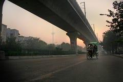 Carrito del triciclo, pedicab, salida del sol brumosa de la mañana de Nueva Deli Imágenes de archivo libres de regalías