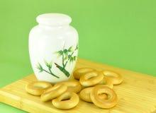 Carrito y galletas de té en fondo verde Imagenes de archivo