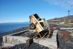 Carro abandonado oxidado quebrado velho de cabeça para baixo na costa de mar Foto de Stock Royalty Free