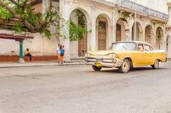 Carro amarelo americano clássico na rua de Havana Fotos de Stock Royalty Free