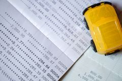 Carro amarelo do brinquedo colocado em uma caderneta bancária do banco na parte-vista Foto de Stock