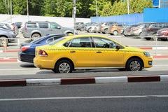 Carro amarelo do táxi estacionado no fundo da passagem nos carros da estrada imagem de stock