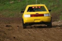 Carro amarelo na trilha que vai rapidamente e sujeira de jogo no ar Imagens de Stock