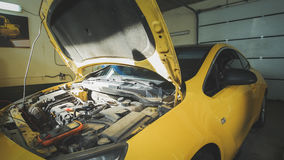 Carro amarelo no auto serviço da garagem - capa aberta - reparação do motor Fotos de Stock Royalty Free