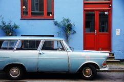 Carro azul ao lado da casa azul com porta e a janela vermelhas Imagem de Stock