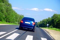 Carro azul na estrada Fotografia de Stock Royalty Free