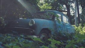 Carro azul soviético retro coberto de vegetação com a grama Carro clássico que oxida em um campo do ` s do fazendeiro imagens de stock royalty free
