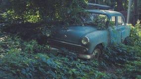Carro azul soviético retro coberto de vegetação com a grama Carro clássico que oxida em um campo do ` s do fazendeiro fotografia de stock royalty free