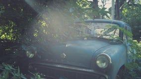 Carro azul soviético retro coberto de vegetação com a grama Carro clássico que oxida em um campo do ` s do fazendeiro fotografia de stock