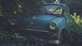 Carro azul soviético retro coberto de vegetação com a grama Carro clássico que oxida em um campo do ` s do fazendeiro imagem de stock royalty free
