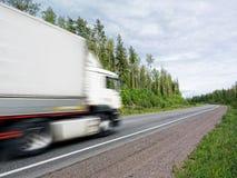 Carro blanco que apresura en la carretera rural, falta de definición de movimiento Imagen de archivo libre de regalías