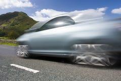 Carro borrado na estrada da montanha Fotografia de Stock