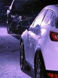 Carro branco oposto ao carro preto na noite na estrada nevado Fotografia de Stock