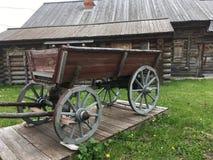 Carro campesino rural ruso del vintage antiguo en la yarda de una casa de madera Imagen de archivo