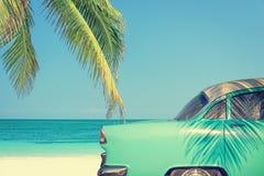 Carro clássico em uma praia tropical com palmeira fotos de stock royalty free