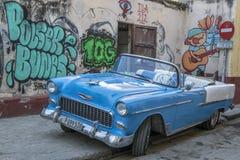 Carro clássico na frente dos grafittis, Cuba imagens de stock