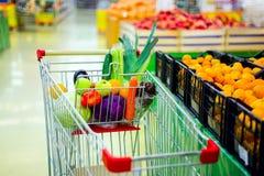 Carro com frutas e legumes frescas no centro de compra Imagens de Stock Royalty Free