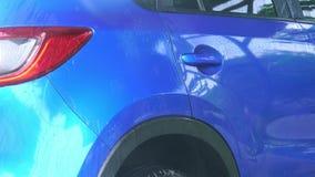 Carro compacto azul de SUV com lavagem do esporte e de projeto moderno com pulverizador de água da arruela de alta pressão no aut video estoque