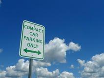 Carro compacto que estaciona somente o sinal com céu azul e nuvens Fotografia de Stock