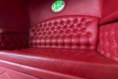Carro con el sofá de cuero rojo Imágenes de archivo libres de regalías