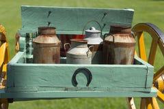 Carro con las latas viejas y oxidadas de la leche Foto de archivo libre de regalías