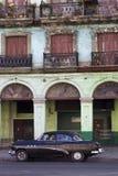Carro cubano preto velho e construção dilapidada Fotos de Stock Royalty Free