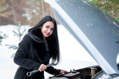 Carro da falha no inverno Menina bonita nova que tenta reparar t foto de stock royalty free