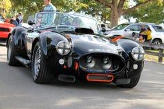 Carro de competência preto clássico velho conduzido na estrada Imagens de Stock Royalty Free