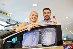 Carro de compra dos pares felizes na feira automóvel ou no salão de beleza Foto de Stock