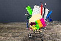 Carro de compras con las fuentes de escuela De nuevo a escuela foto de archivo libre de regalías